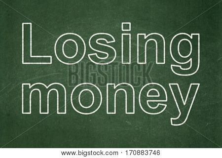 Money concept: text Losing Money on Green chalkboard background