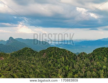 Panoramic view of the mountains covered with tropical forests and the sea on the horizon, Langkawi Island, Malaysia. Dramatic sky with clouds.