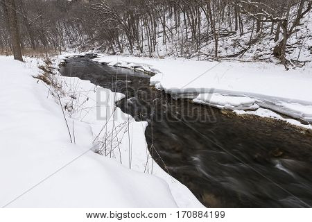 A river in the woods during winter.