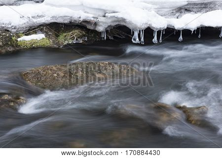 A river flowing through rapids in winter.