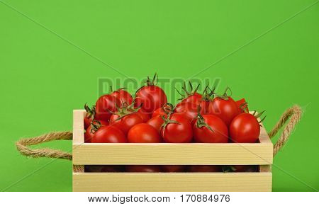 Red Cherry Tomatoes In Wooden Box Over Green