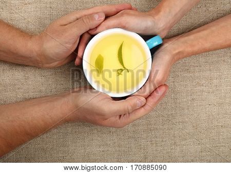 Man And Woman Hands Hold Full Green Tea Cup