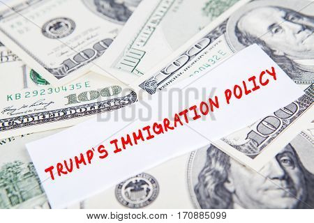 Heap of dollar banknotes with text of Trump's Immigration Policy
