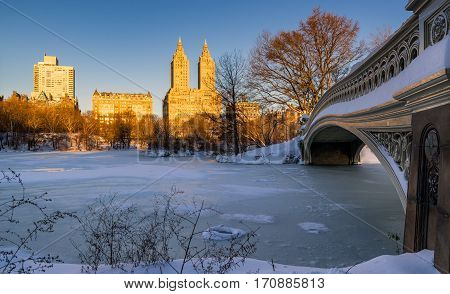 Central Park winter sunrise on the frozen Lake with the Bow Bridge and Upper West Side buildings. Wintertime in Manhattan New York City