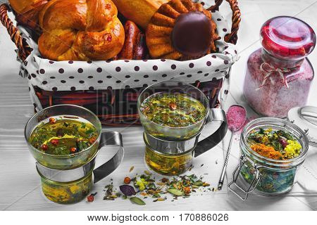 Morning breakfast for two. Herbal tea in the cups and pastries bread rolls in a wicker basket. Herbal tea in the pot strawberry sugar. Dry tea is scattered on a white wooden table.