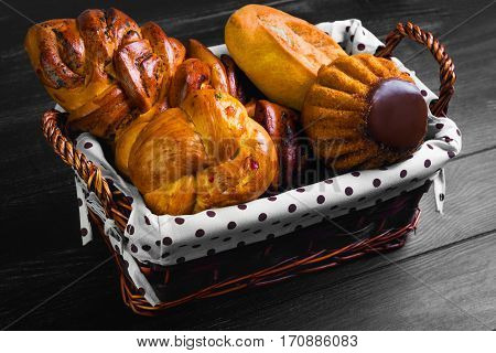 Assortment of fresh pastries buns bread - large loaf Pie with poppy seeds buns with candied fruit cupcake bun with chocolate in special wicker basket for pastries bread. Black wooden background.