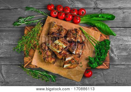 Meat Pork ribs on a barbecue grill on the board on paper. Spices for pork ribs grilled rosemary thyme parsley lettuce cherry tomatoes on a gray wooden background rustic. Top view flat lay.