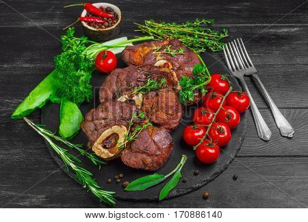 Ready-cooked beef meat Osso buco Veal shank on black stone board. Ingredients for Osso buco thyme parsley rosemary lettuce pepper sage. Dark wooden background.
