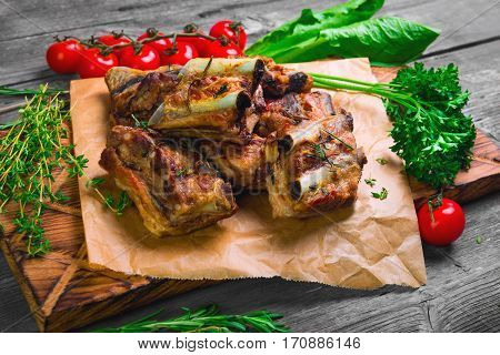 Meat Pork ribs on a barbecue grill on the board on paper. Spices for pork ribs grilled rosemary thyme parsley lettuce cherry tomatoes on a gray wooden background rustic.