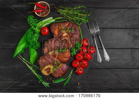 Ready-cooked beef meat Osso buco Veal shank on black stone board. Ingredients for Osso buco thyme parsley rosemary lettuce pepper sage. Dark wooden background. Top view.