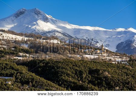 Saint-Sauveur village near Embrun with winter view on Les Orres ski resort. Hautes-Alpes Southern French Alps France