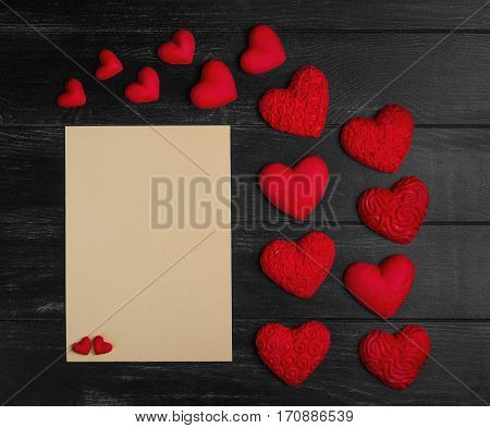 Card to Valentine's Day. Paper for text congratulations letter. Heart from red marzipan. Heart with pattern and heart sleek black wooden background.Top view.