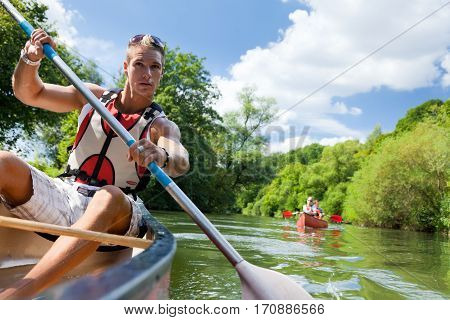 young people canoeing on the neckar river in germany.