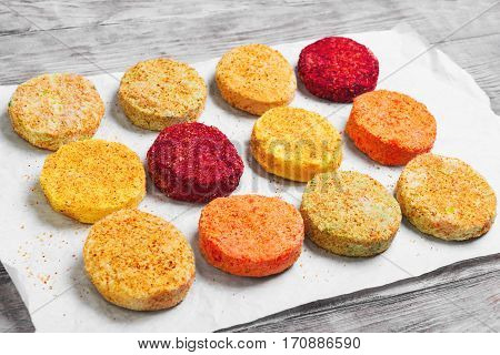 Raw Vegetables patties cutlets for vegan burgers on white paper. Mix stack vegetables fresh burgers patties cutlets. Light white wooden background.