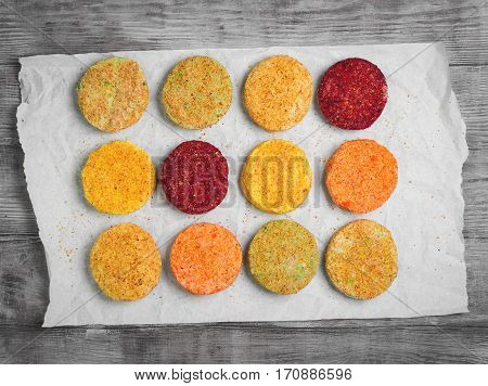 Raw Vegetables patties cutlets for vegan burgers on white paper. Mix stack vegetables fresh burgers patties cutlets. Light white wooden background.Top view.