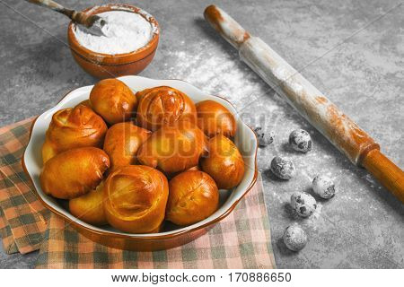 Preparing buns bread. Ingredients for cooking homemade buns bread wheat flour in bowl quail eggs wooden rolling pin. Fresh buns in a ceramic bowl on a gray concrete background.