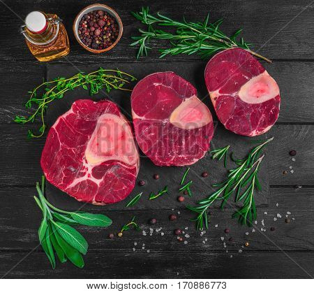 Raw meat beef veal shank slices meat for Osso Buco cooking on dark black wooden background. Ingredients for beef meat Osso Buco sage leaves thyme rosemary pepper salt pepper vegetable oil. Top view.