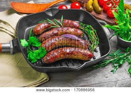 Grilled fried sausages kupaty on a cast iron skillet grill greens to grilled fried sausages arugula basil coriander thyme rosemary tomatoes.. Scapula for fried sausages. Grey wooden background.