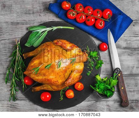 Whole Roasted Chicken with Vegetables. The ingredients for chicken baked golden cherry tomatoes herbs spices thyme sage rosemary cilantro arugula knife. Light wooden background.