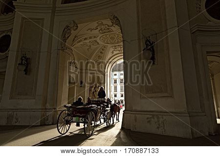 Traditional horse riding in a Fiaker through the gateway of Michaelertrakt in the Inner City of Vienna, Austria.