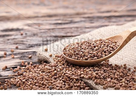 raw buckwheat in a wooden spoon on a dark brown wooden background