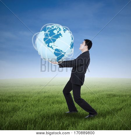 Young asian businessman holding an earth planet on the green field