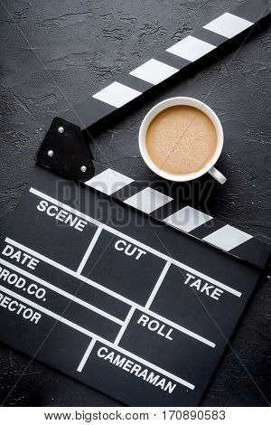 Screenwriter desktop with movie clapper board on dark background top view