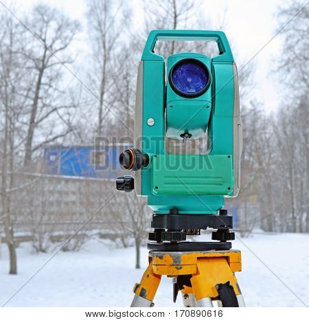 Theodolite on support near the building site in winter
