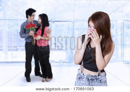 Image of brunette girl crying and jealous while looking at romantic young couple