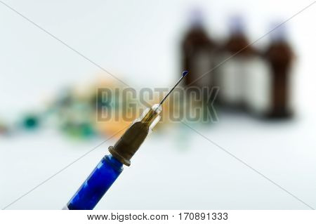 photo of injection,syringe with liquid drop on its needle,nozzle over blurry laboratory background.