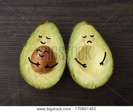 An avocado parent and child in embrace beside another avocado who is sad that is it without a child or baby.