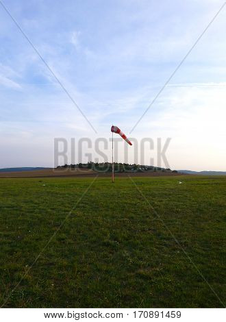 Photo of a windsock standing on a grassy airfield