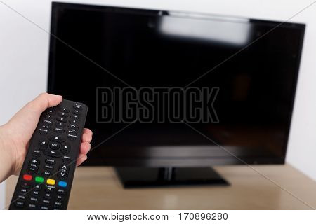 Hand using remote control turned off or turning on the TV