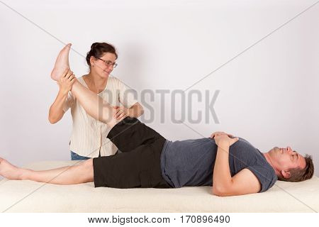 Man receives bowen massage treatment for his legs. Bowen is a holistic system of healing.