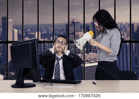 Young female employee is shouting at his manager through megaphone while working with a computer in the office near the window