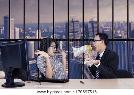 Young male manager shouting at his secretary through megaphone while working with a computer in the office near the window
