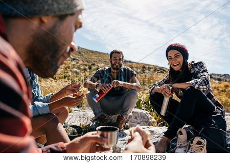 Group Of People Relaxing And Eating During Hike