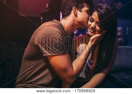 Young couple in love at the night club. Man kissing his girlfriend sitting at lounge bar.
