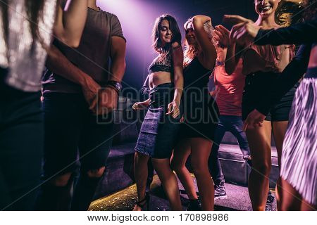 Group of party people dancing in a disco. Young woman with friends dancing at nightclub.