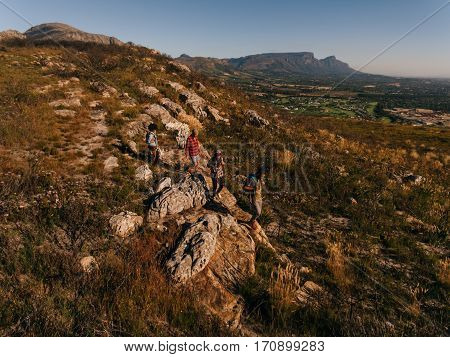 Young People Through Extreme Terrain In Countryside