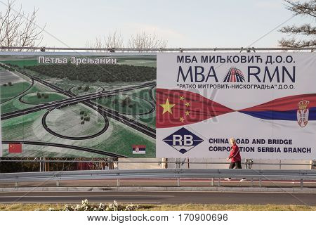 BELGRADE SERBIA - DECEMBER 25 2014: Woman passing by a billboard promoting Chinese investments in Serbia near the newly opened Pupin bridge over the Danube