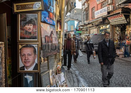 ISTANBUL TURKEY - DECEMBER 28 2015: People passing by portraits of Kemal Ataturk and Recep Tayyip Erdogan current president of Turkey