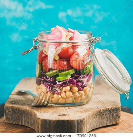 Healthy take-away lunch jar. Vegetable and chickpea sprout vegan salad in jar on wooden board, bright blue wall at background, selective focus, square crop. Clean eating, vegetarian, dieting concept