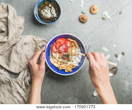 Yogurt, granola, seeds, fresh and dry fruits and honey in blue ceramic bowl in woman' s hands over grey concrete background, top view. Clean eating, detox, dieting, vegetarian food concept