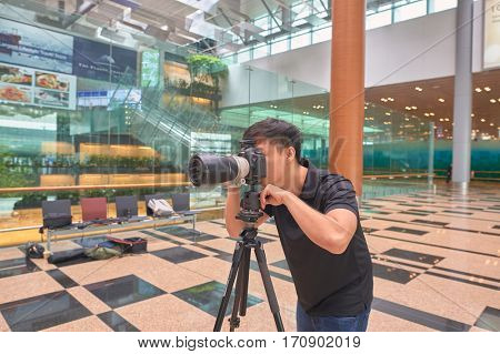 SINGAPORE - CIRCA NOVEMBER, 2015: man taking photo at Changi Airport. Changi Airport, is the primary civilian airport for Singapore, and one of the largest transportation hubs in Southeast Asia.