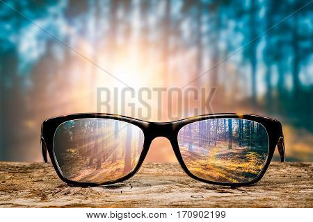 glasses focus background wooden eye vision lens eyeglasses nature reflection look looking through see clear sight concept transparent sunrise prescription sunset vintage sunny sun retro - stock image