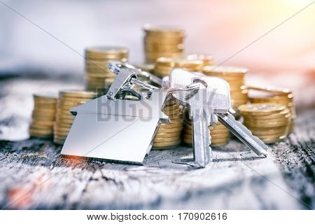 House key on a house shaped keychain and coin on wooden table. Concept for real estate or renting home.