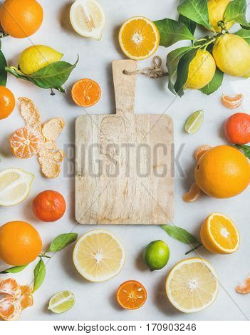 Variety of fresh citrus fruit for making juice or smoothie and wooden chopping board in center over light grey marble background, top view, copy space. Healthy eating, vitamin, clean eating concept