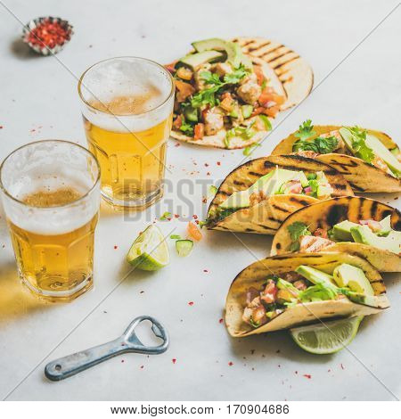 Healthy corn tortillas with grilled chicken fillet, avocado, fresh salsa, limes, beer in glasses over light grey marble background, selective focus, square crop. Gluten-free, weight loss concept