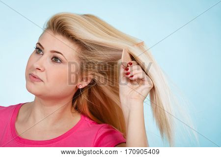 Woman Brushing Her Long Blonde Hair With Comb